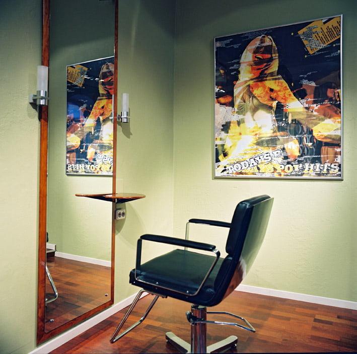 poster på väggen ovanför frisörstol och spegel